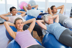Smiling people stretching on exercise balls in gym Stock Photography