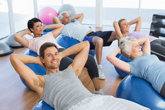Smiling people stretching on exercise balls in gym Royalty Free Stock Photos