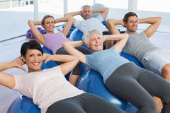 Smiling people stretching on exercise balls Stock Photography