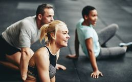 Smiling people taking a break after working out together. Diverse group of smiling people in sportswear sitting together on a gym floor taking a break from their stock images