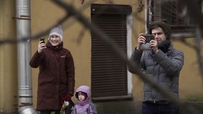 Smiling people taking photo using smartphone at city street. Smiling caucasian people with little kid in warm clothes taking photo using smartphone at city stock video