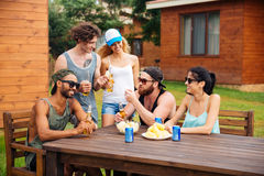 Smiling people talking and drinking beer at the table outdoors stock image