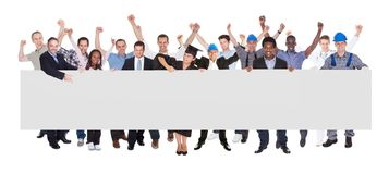 Smiling people with various occupations holding blank billboard. Full length portrait of smiling people with various occupations holding blank billboard over royalty free stock image