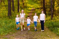 Smiling people in white t-shirts go through the woods in the summer. Mothers and children. Outdoors stock images