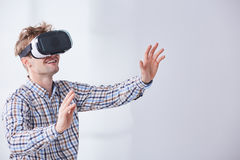 Smiling person doing gestures. While playing cyber game in virtual reality Royalty Free Stock Photo