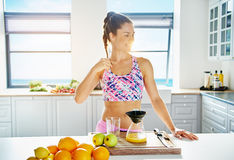 Smiling person doing juice with different fruits. Young happy woman doing fresh with liquidizer at the kitchen. Horizontal indoors shot Stock Image