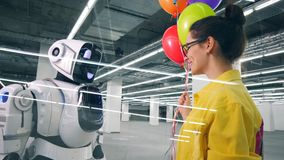 Smiling person gives many balloons to automated cyborg. stock video