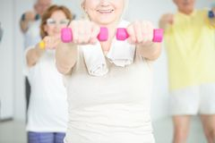 Smiling person working out. Close-up of smiling elderly person working out with pink dumbbells Royalty Free Stock Image