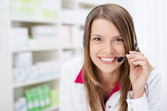 Smiling pharmacist chats to a patient on a headset Royalty Free Stock Photos