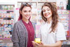 Smiling pharmacist and client in front of a drugstore desk Stock Photos