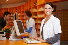 Smiling pharmacist at computer. Smiling pharmacist working at computer in a pharmacy Royalty Free Stock Photos