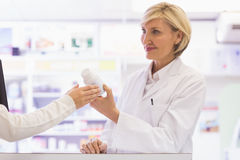 Smiling pharmacist and customer discussing a product Stock Images