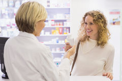 Smiling pharmacist and customer discussing a product Royalty Free Stock Image