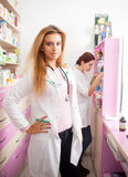 Smiling pharmacist in front and the second one looking in the ba Royalty Free Stock Images