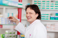 Smiling pharmacist in front of shelf Royalty Free Stock Photos
