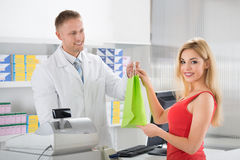 Smiling Pharmacist Giving Medicines To Customer Stock Photos