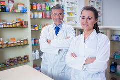 Smiling pharmacist and his trainee with arms crossed Royalty Free Stock Images