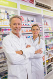 Smiling pharmacist and his trainee with arms crossed Stock Photos