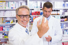 Smiling pharmacist holding a box of pills Royalty Free Stock Photos