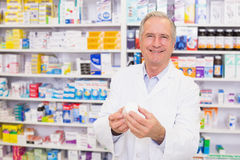 Smiling pharmacist holding a box of pills Stock Photo