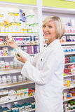 Smiling pharmacist holding boxes of medicine Stock Images