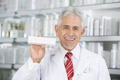 Smiling Pharmacist Holding Medicine Box Against Shelves Royalty Free Stock Image