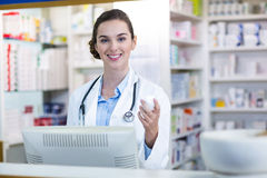 Smiling pharmacist holding medicine container in pharmacy Stock Photo