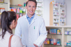 Smiling pharmacist holding a paper bag looking at camera Royalty Free Stock Photos