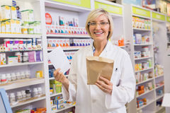 Smiling pharmacist holding prescription and envelope Royalty Free Stock Photo