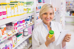 Smiling pharmacist holding prescription and medicine Stock Photo