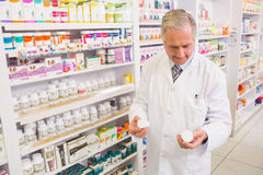 Smiling pharmacist looking at medications Stock Photo