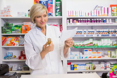 Smiling pharmacist looking at prescription and medicine Stock Image