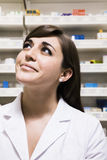Smiling pharmacist looking up in a pharmacy Stock Image