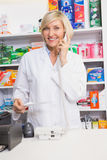 Smiling pharmacist on the phone reading prescription Stock Images