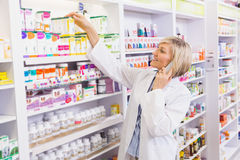 Smiling pharmacist phoning and taking medicine from shelf Royalty Free Stock Image