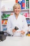 Smiling pharmacist scanning box of medicine Stock Images