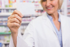 Smiling pharmacist showing calling card Royalty Free Stock Image