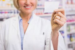 Smiling pharmacist showing calling card Royalty Free Stock Photos