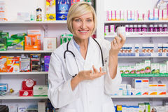 Smiling pharmacist showing medication at camera Royalty Free Stock Images