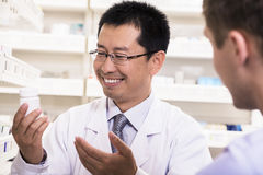 Smiling pharmacist showing prescription medication to a customer Royalty Free Stock Image
