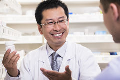 Smiling pharmacist showing prescription medication to a customer Royalty Free Stock Images