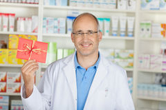 Smiling pharmacist showing red coupon Royalty Free Stock Photo