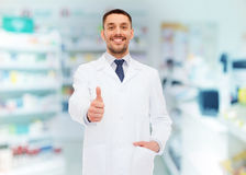 Smiling pharmacist showing thumbs up at drugstore Royalty Free Stock Images