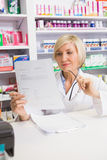 Smiling pharmacist thinking and reading prescription Royalty Free Stock Photography