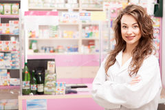 Smiling pharmacist in uniforme in front of the desk Stock Photos