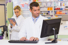 Smiling pharmacist using computer stock photography