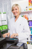 Smiling pharmacist using computer Stock Photos