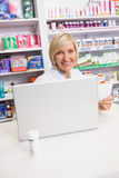 Smiling pharmacist using laptop and holding prescription Royalty Free Stock Image
