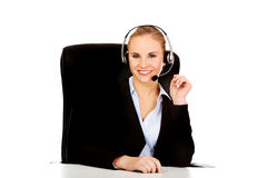 Smiling phone operator in headphones sitting  behind the desk Royalty Free Stock Photo