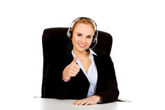 Smiling phone operator in headphones sitting  behind the desk Stock Photo